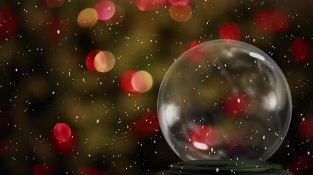 snow globe : Animation of Christmas snow globe with snow falling and fairy lights on Christmas tree flickering in the background Stock Footage