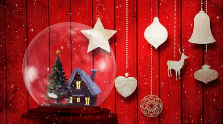 snow globe : Animation of Christmas snow globe with Christmas tree and house inside and snow falling with Christmas decorations on red background