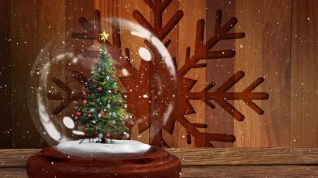 snow globe : Animation of Christmas snow globe with Christmas tree inside and snow falling with snowflake Christmas decoration on wooden background Stock Footage