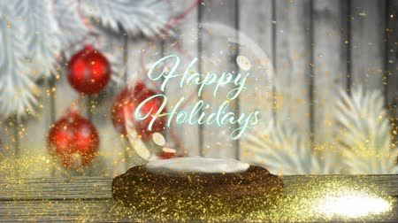 komet : Animation of the words Happy Holidays written in blue letters in Christmas snow globe with shooting star in yellow, Christmas baubles and snow falling on wooden boards and white background
