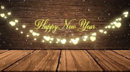 christmas dekorasyon : Happy New Year Message in gold appearing on wooden background with golden hearts. Festive Christmas time. Stok Video