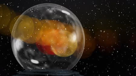 snow globe : Animation of Christmas snow globe with snow falling and defocussed yellow spots of light in the background