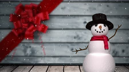 espírito : Animation of winter scenery with snow falling, Christmas decoration with red ribbon and snowman on grey wooden boards in the background
