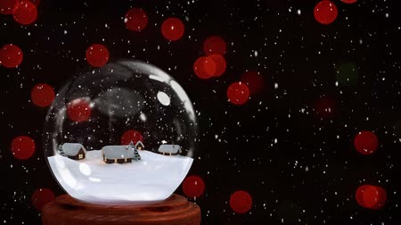 snow globe : Animation of Christmas snow globe with houses inside, snow falling and red fairy lights flickering in the background Stock Footage