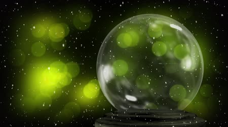 snow globe : Animation of Christmas snow globe with snow falling and defocussed green spots of light in the background