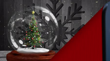 snow globe : Animation of Christmas snow globe with Christmas tree inside with snowflake on wooden boards and snow falling being revealed from underneath blue background with snowflakes