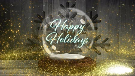 snow globe : Animation of the words Happy Holidays written in blue letters in Christmas snow globe with shooting star in yellow, snowflake and snow falling with wooden boards in the background Stock Footage