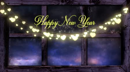 changing lights : Animation of the words Happy New Year written in yellow letters with a glowing string of fairy lights and fireworks in the background Stock Footage