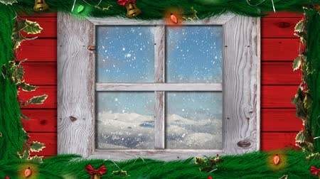 падуб : Animation of winter scenery seen through window with snowflakes falling in countryside and Christmas decorations with holly and fairy lights in the foreground Стоковые видеозаписи