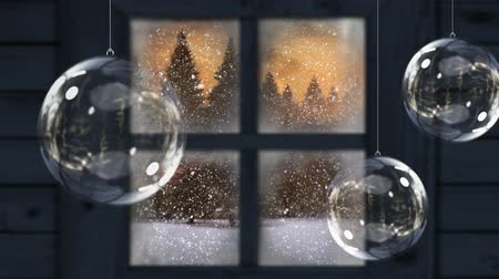 seasons changing : Animation of winter scenery seen through window with snowflakes falling and fir trees in countryside with three Christmas glass baubles hanging in the foreground