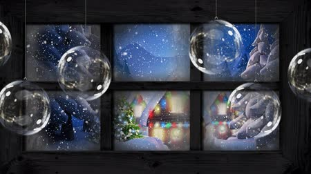 seis : Animation of winter scenery seen through window with snowflakes falling, house and fir trees in countryside with six Christmas glass baubles hanging in the foreground