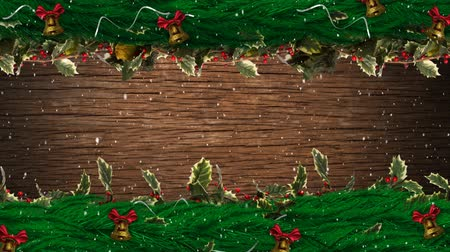 падуб : Animation of snow falling with Christmas decorations, holly, berries and bells on top and bottom on wooden background