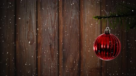 seasons changing : Animation of snow falling with red Christmas bauble on wooden background
