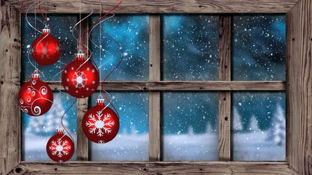 seasons changing : Animation of winter scenery seen through window with snowflakes falling in countryside with five red Christmas baubles in the foreground