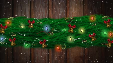 changing lights : Animation of snow falling with Christmas decorations, fairy lights and bells on wooden background Stock Footage