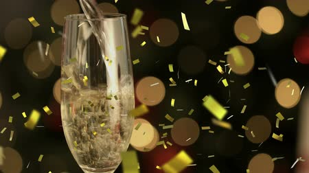 changing lights : Animation of champagne being poured into a glass with golden confetti falling during New Year Eve celebrations