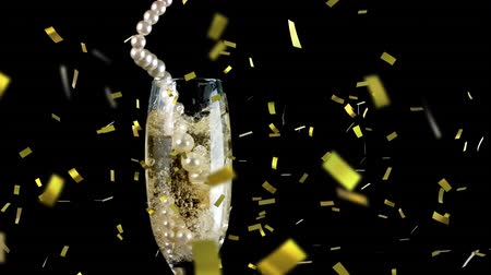 champagne flute : Animation of string of pearls falling into champagne glass with golden confetti falling during New Year Eve celebrations