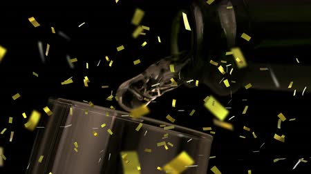 champagne flute : Animation of champagne being poured into a glass from a bottle with golden confetti falling during New Year Eve celebrations on black background Stock Footage