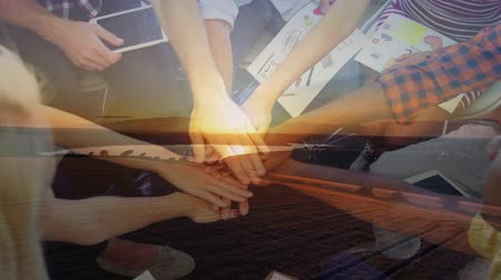 empilhamento : Animation of a high angle view of diverse group of male and female office colleagues stacking their hands and celebrating success with sunset in the background