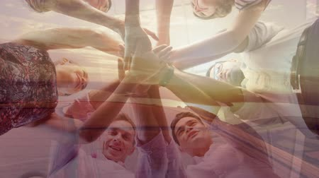 empilhamento : Animation of a low angle view of diverse group of young male and female office colleagues stacking their hands, smiling and celebrating success with sunset in the background Vídeos