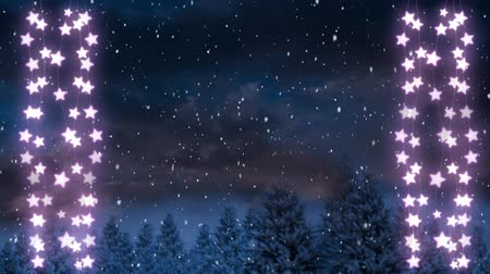 seasons changing : Animation of winter scenery with two glowing strings of Christmas fairy lights and snow falling in the background Stock Footage