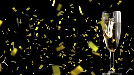 champagne flute : Animation of piece of gold falling into a full champagne glass with golden confetti falling during New Year Eve celebrations on black background Stock Footage