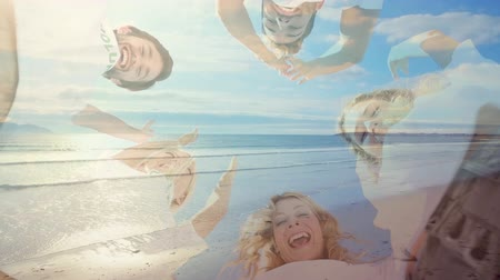 empilhamento : Animation of low angle view of diverse group of male and female friends stacking their hands, smiling and celebrating success with sea and sky in the background
