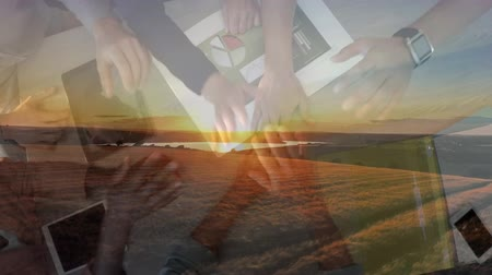 stapelen : Animation of an overhead view of a group of male and female office colleagues stacking their hands and celebrating success with sunset in the background Stockvideo