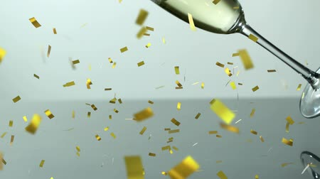 flet : Animation of champagne glass falling and spilling champagne with golden confetti falling during New Year Eve celebrations on white background