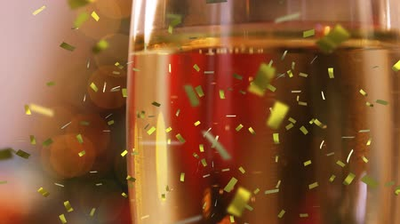 champagne flute : Animation of a full champagne glass with golden confetti falling during New Year Eve celebrations Stock Footage