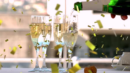 flet : Animation of hand of person pouring champagne from a bottle into champagne glasses with golden confetti falling during celebrations Wideo