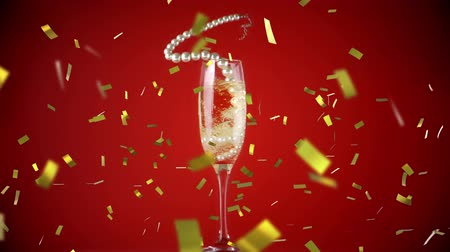 champagne flute : Animation of string of pearls falling into champagne glass with golden confetti falling during New Year Eve celebrations on red background Stock Footage