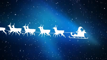sob : Animation of a white silhouette of Santa Claus in sleigh being pulled by reindeers from right to left at Christmas time with snow falling on glowing blue background