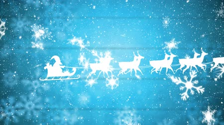 esquerda : Animation of a white silhouette of Santa Claus in sleigh being pulled by reindeers from left to right at Christmas time with snow falling and snowflakes on blue background