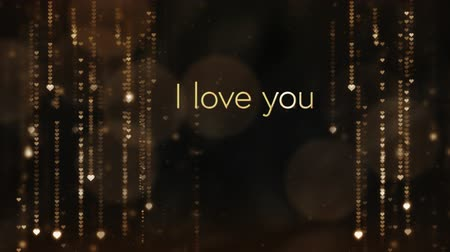 i love you : Animation of the words I Love You written in brown letters with gold shimmering lights in the background