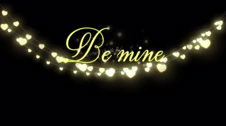 ser : Animation of the words Be Mine written in yellow with glowing string of fairy lights on black background Stock Footage