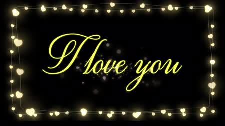 я тебя люблю : Animation of the words I Love You written in yellow with glowing fairy lights frame on black background