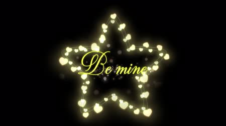 luty : Animation of the words Be Mine written in yellow with glowing fairy lights star on black background Wideo