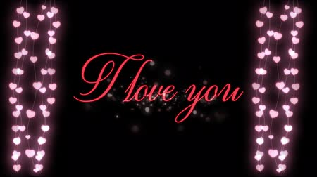 i love you : Animation of the words I Love You written in pink with glowing strings of fairy lights on black background