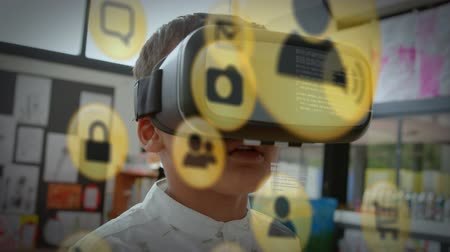 social change : Animation of yellow network connection and data sharing icons with a close up of a boy wearing a VR headset in a school classroom in the background