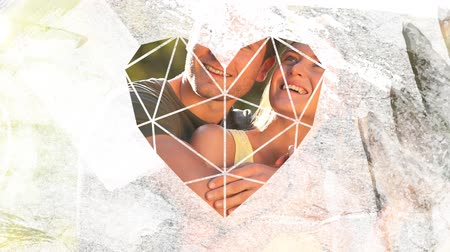 visto : Animation of a happy Cacuasian couple embracing and smiling outdoors in the sun with trees behind them, seen through a white heart shaped window in the foreground Stock Footage