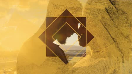 visto : Animation of the side view close up of a mixed race couple standing on a beach by the sea at sunset kissing, seen through a yellow star shaped window in the foreground