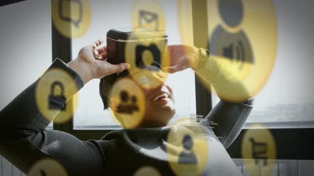 spojovací : Animation of yellow network connection and data sharing icons with a Caucasian man sitting back and smiling with a VR headset on the back of his head in the background
