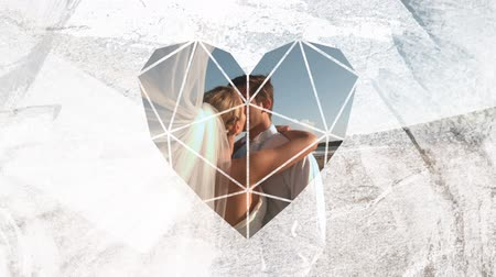visto : Animation of the side view of a Caucasian just married couple kissing on a beach with the bridal veil blowing towards the camera, seen through a white heart shaped window in the foreground Stock Footage