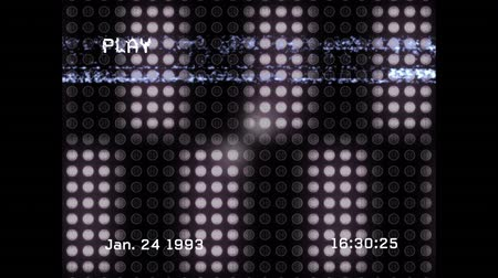 behind bars : Animation of a screen with the word play, the date and time written in white text and bands of interference, with 3d white vertical bars moving in formation behind a red black circular grid