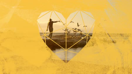 visto : Animation of a man running waving his arms on a beach and a flock of birds flying over the sea at sunset in slow motion, seen through a yellow heart shaped window in the foreground