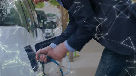 tankowanie : Animation of man charging an electric car, network of connections moving in the foreground. Environment and eco friendly car engineering, Wideo