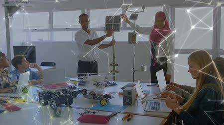 inventing : Animation of a mixed race male and a female engineer wearing a hijab presenting an eco friendly solar panel to their students, network of connections moving in the foreground. Environment and eco friendly car engineering, Stock Footage