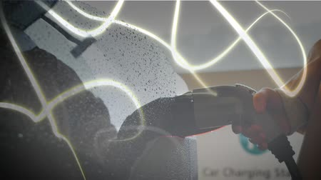 tankowanie : Animation of person charging an electric car, white lines of network of connections moving in the foreground. Environment and eco friendly car engineering, Wideo