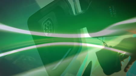 auta : Animation of hand of a woman charging an electric car, green and orange glow moving in the foreground. Environment and eco friendly car engineering,